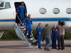 The space shuttle Endeavour crew members  walk off a plane as they arrive at Kennedy Space Center on Thursday.