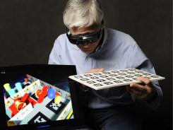 Steven Feiner wears Vuzix Wrap augmented reality eyewear during a demonstration of an augmented reality marble labyrinth game.