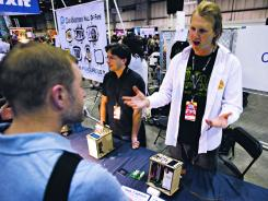 Josh Perfetto, center, and Tito Jankowski, right, co-founders of OpenPCR, explain their device to a group of curious onlookers at  their table at the Makers Faire in San Mateo, Calif.