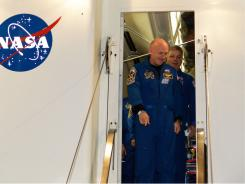 Mark Kelly, front, and Gregory Johnson exit the crew transport after Endeavour landed at Kennedy Space Center on Wednesday.
