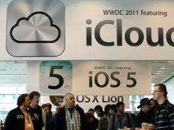 Attendees walk by signs for the new iCloud and iOS5 during Monday's Apple World Wide Developers Conference.