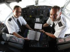 Alaska Airlines captains Randy Kleiger and Stephen Lemley show the difference between one of their many manuals and the iPad.