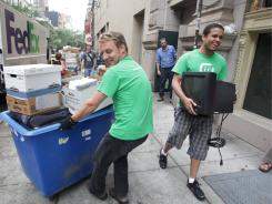 John Kirsch, left, and Vadhil Amadis of The 4th Bin, a startup electronic waste collection and recycling company, wheel old hardware to their truck in New York City on June 21, 2011.