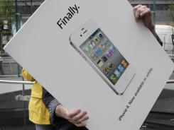 A store employee carries an advertisement for the white iPhone in the Apple store on New York's Upper West Side in April.