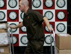 In this file photo, UPS delivery man Chris Carhart of South Boston, wheels packages past a store window featuring clocks.  A yearlong experiment with the electric grid may make plug-in clocks and devices like coffeemakers run up to 20 minutes fast.