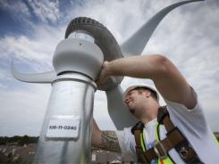 Taylor Tompkins installs the final yawl cover over a Skystream Wind Turbine near the Lady Bird Johnson Middle School in Irving, Texas.