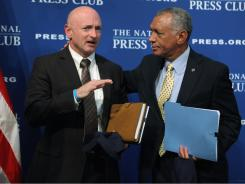 Astronaut and space shuttle commander Capt. Mark Kelly, left, talks with NASA Administrator Charles Bolden Jr. after both men addressed the National Press Club Newsmakers Luncheon Friday in Washington.