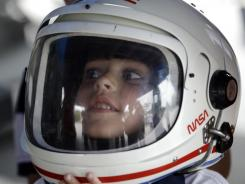 Xavier Ladik of Philadelphia tries on a helmet at the Kennedy Space Center Visitor Complex on Thursday.