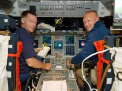 Astronauts Chris Ferguson and Doug Hurley are pictured at the commander's station and pilot's station, respectively, on the flight deck of the Earth-orbiting NASA space shuttle Atlantis.
