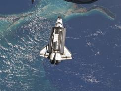The space shuttle Atlantis is seen over the Bahamas prior to a perfect docking with the International Space Station.