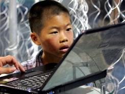 A child stares intently at a Lenovo laptop in Beijing, China.