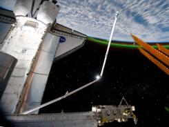 The Aurora Australis ring planet earth as the docked space shuttle Atlantis' cargo bay and the solar array panel of the International Space Station are seen Thursday.