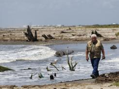 Forrest Travirca III walks along Port Fourchon Beach on June 28 as he searches for artifacts from Pre-historic American-Indian settlements in Caminada Headland, La.