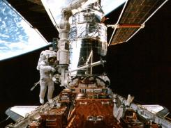 Astronaut Steven Smith works  on the Hubble Space Telescope in this photograph from 1997.