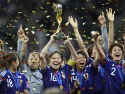 Japan players celebrate with the trophy after winning the final match between Japan and the United States at the Women's Soccer World Cup in Frankfurt, Germany.