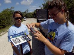 "Arianne Lujon, left, and Lydia Templin test QR codes on signs at J.N. ""Ding"" Darling National Wildlife Refuge on Sanibel Island, Fla."