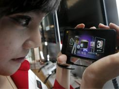 A model looks at a LG Electronics' Optimus 3D phone during a press conference in Seoul, South Korea. Watching videos on your phone can really tax your data plan.