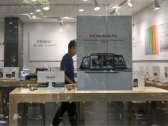 A shopkeeper dressed as an Apple store employee looks out from a window of a shop masquerading as a bona fide Apple store in China.