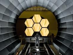 A NASA engineer watches mirrors of the Webb Space Telescope being prepared for testing at  Marshall Space Flight Center.