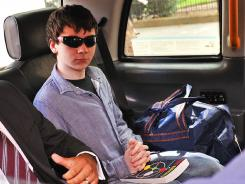 Jake Davis, 18, leaves in a taxi from Westminster Magistrates Court in London.