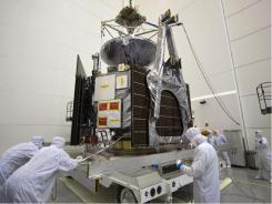 Technicians in Titusville, Fla., disconnect the Juno spacecraft from its transport in June. The $1.1 billion mission launches today and should arrive at Jupiter in 2016.