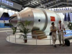 In this 2010 photo, visitors sit besides a model of Chinese made Tiangong 1 space station at the 8th China International Aviation and Aerospace Exhibition in Zhuhai city, south China, Guangdong province.