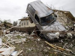 A vehicle rests on a tree after an overnight tornado in Tushka, Okla. Federal grant money will help the community rebuild its broadband infrastructure.