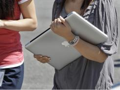 An Apple employee carries an Apple laptop between buildings at Apple headquarters in Cupertino, Calif., Thursday.