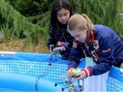Students Marissa Suto and Melina Pickard fix a robot sub.