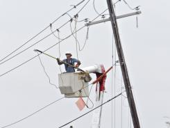 A line worker with South Carolina Electric and Gas repairs a power pole that was snapped by the first wind and rain from Hurricane Irene.