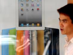 A man walks past a poster showing the Apple iPad 2.