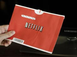 A Netflix customer holds up a movie in Palo Alto, Calif.