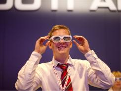 A man puts on a double set of 3D glasses while watching a massive video wall at electronics giant LG's booth at the IFA tech trade show in Berlin.