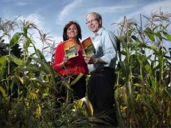 Farmers' Almanac editor Sondra Duncan and publisher Peter Geiger pose in a corn field with the 2012 edition of the almanac.