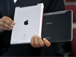A lawyer holds an Apple iPad and a Samsung Tablet-PC at a court in Duesseldorf, Germany.