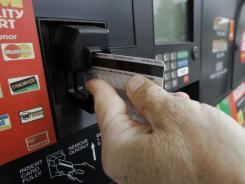A customer swipes his credit card at a gas station pump.