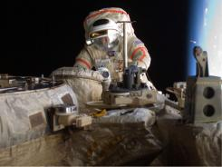 This 2009 photo shows Astronaut Michael Fincke performing maintenance on the International Space Station.  The space station crew rode out a threat of collision with a debris cloud in a Soyuz space capsule on March 12, 2009.
