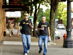 Ryan Kuder, left,  and Gadi Shamia of Bizzy walk through downtown Portland, Ore.