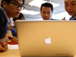Apple employees show a laptop to a customer. left, during the opening of the first Apple retail store in Hong Kong on Sept. 24.