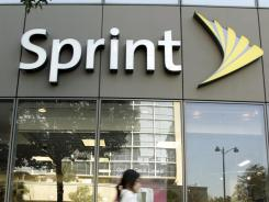 A woman walks past a Sprint store in Los Angeles.