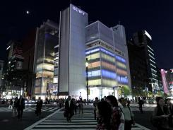 People cross an intersection in front of the Sony Building in Tokyo on Thursday.