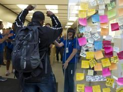 Sticky notes in memory of Steve Jobs line the glass outside the Apple Store in Philadelphia, PA Friday morning as Anthone Moore, 26, of Philadelphia walks in first to buy the iPhone 4s to the cheers of Apple employees.