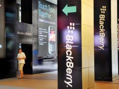 A man walks past a large BlackBerry advertisement in Hong Kong.