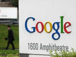 A pedestrian walks by a sign that is outside of the Google headquarters in Mountain View, Calif.