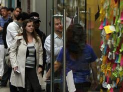 Customers wait in line to purchase the new iPhone 4S in view of a makeshift memorial to deceased Apple co-founder Steve Jobs outside of an Apple store.