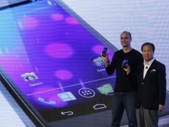 Google's top mobile executive Andy Rubin, left and J.K. Shin, president and head of mobile communications business from Samsung, hold the new Galaxy Nexus smartphone.