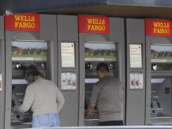 Customers use Wells Fargo Bank ATM machines in Santa Clara, Calif.