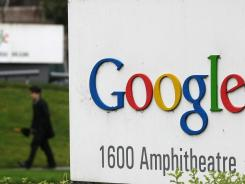 A pedestrian walks by a sign outside of the Google headquarters in Mountain View, Calif.