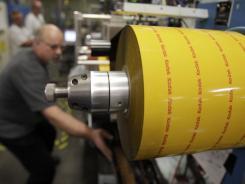 In this May 26, 2011 file photo, Kodak employee Dan Vandelinder operates a machine that packages medium format film in Rochester, N.Y.