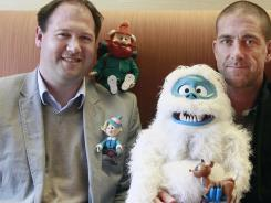 Microsoft executives Aaron Lilly, left, and  Sean Carver, pose with figures from the animated show 'Rudolph the Red Nose Reindeer.'